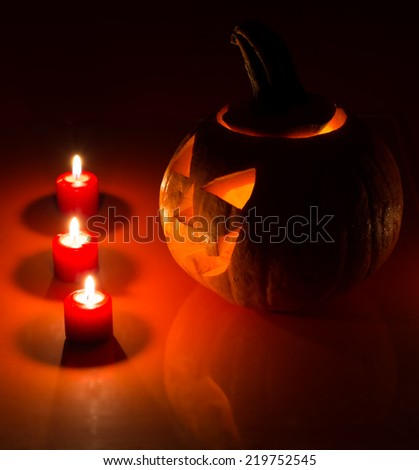 Glowing halloween pumpkin with burning candles and reflection - stock photo