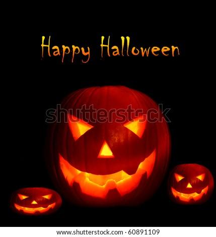 Glowing Halloween pumpkins isolated on black - stock photo