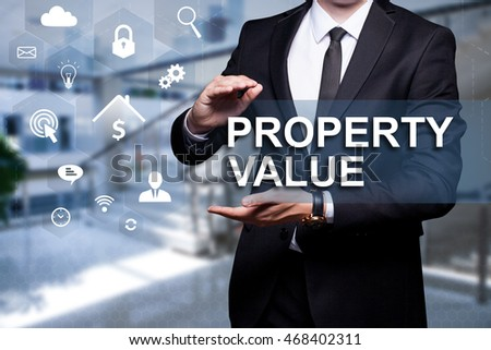 "Glowing icon ""Property Value"" in the hands of a businessman. Business concept. Internet concept."