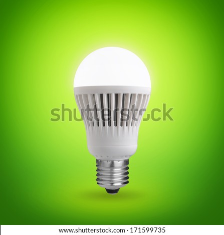Glowing LED bulb on green background  - stock photo
