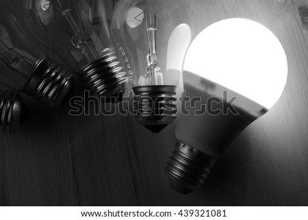 Glowing LED lamp including incandescent lamps on a wooden table - stock photo