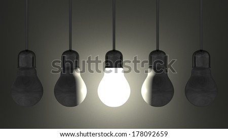 Glowing light bulb among dead ones in lamp sockets hanging on wires on dark gray textured background