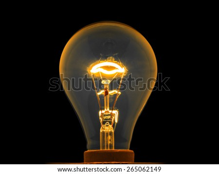 glowing light bulb by electrical current in metal filament, isolated - stock photo