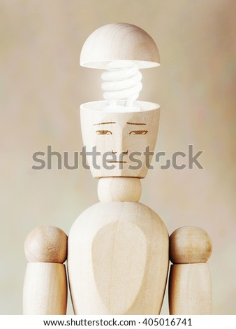 Glowing light bulb in the human head. Concept of genius. Abstract image with wooden puppet - stock photo