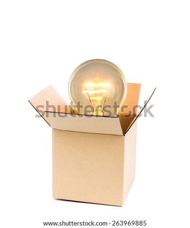 Glowing light bulb over open cardboard box - stock photo
