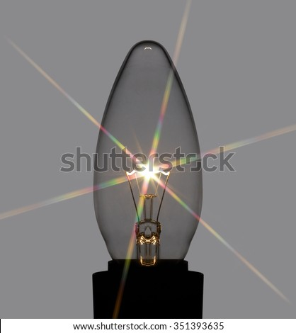 glowing light bulb with star filter in dark back - stock photo