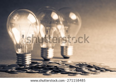 Glowing light bulbs and pile of coins