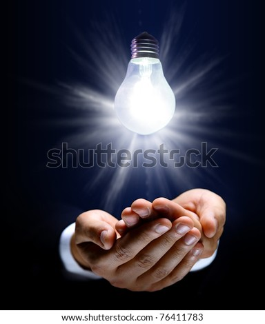 Glowing lightbulb and hand - stock photo