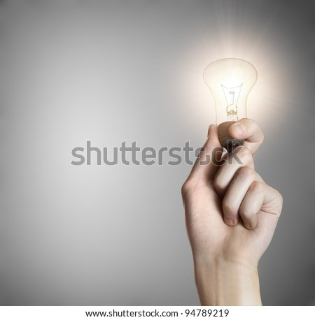 Glowing lightbulb in a hand on gray background with copyspace - stock photo