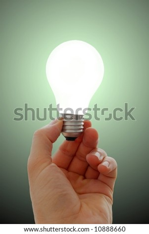 Glowing lightbulb in hand - stock photo
