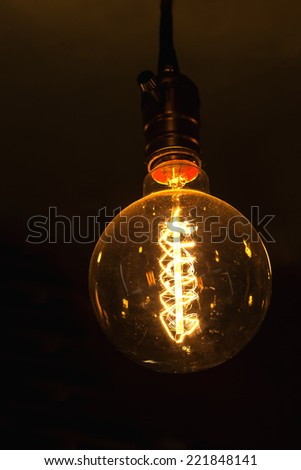 glowing round bulb tungsten lamp, heated filament light, incandescent illumination on dark background - stock photo