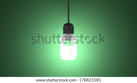 Glowing spiral light bulb in lamp socket hanging on dark green textured background