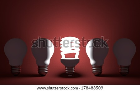 Glowing spiral light bulb in row of dead incandescent ones on dark red textured background. Front view