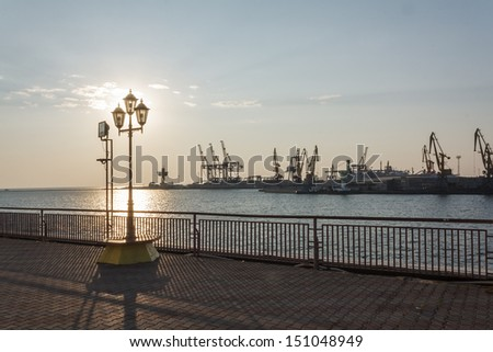 Glowing street lamp in port on Black sea sunset