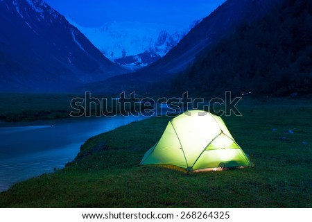 Glowing tent stands on the banks of a mountain stream, amid high mountains and snow-capped peaks. Twilight, night. - stock photo