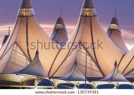 Glowing tents of DIA at sunrise. Denver International Airport well known for peaked roof. Design of roof is reflecting snow-capped mountains. - stock photo
