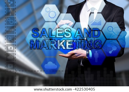 "Glowing text ""Sales And Marketing"" in the hands of a businessman. Business concept. Internet concept."