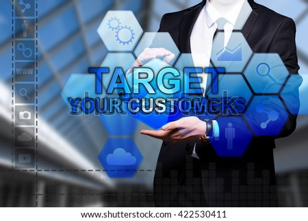 "Glowing text ""Target Your Customers"" in the hands of a businessman. Business concept. Internet concept."