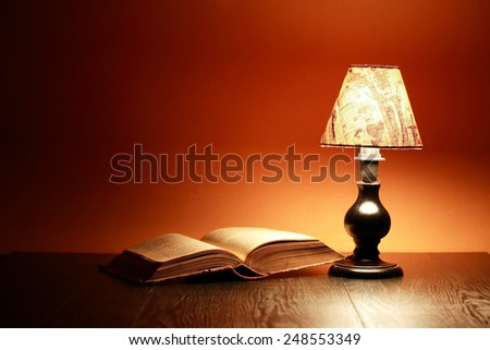 Glowing vintage table lamp near open old book - stock photo