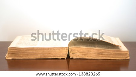 Glowing warm light originating from the pages of an old book. The book pictured is a dictionary. - stock photo