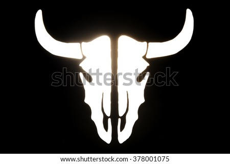 glowing , white silhouette of the animal's skull with horns on a black background
