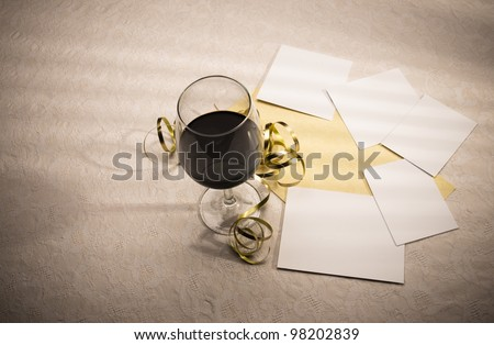 Glowing wine glass, decorations, invitation card and blank photograph frames. These spaces can be used to add images and invitation text as required. There is copy space at the left for plenty of text - stock photo