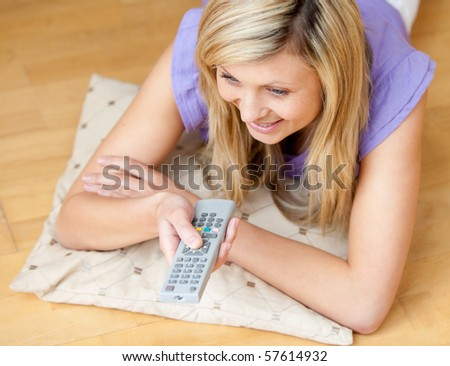 Glowing woman watching TV holding a remot lying on the floor - stock photo