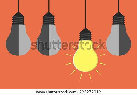 Glowing yellow light bulb hanging among three gray dull ones - stock photo