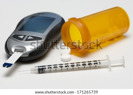 Glucometer, diabetes medication, and insulin syringe. - stock photo