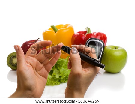 glucometer for glucose level blood test in hand and healthy organic food on a white background. Diabetes concept