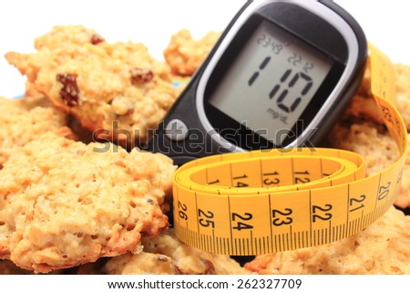 Glucometer, oatmeal cookies and tape measure lying on colorful plate, concept for diabetes, slimming and healthy nutrition - stock photo
