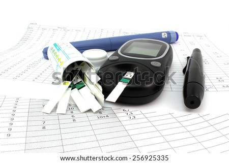 Glucometer test strips and insulin on document - stock photo