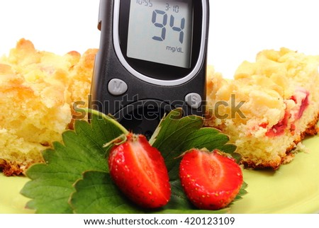 Glucose meter and pieces of fresh baked yeast cake with crumble and strawberries, concept of diabetes, sweet dessert