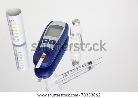 Glucose Meter, Blood sugar testing, test strips, vial, syringe on reflective surface - stock photo