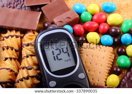 Glucose meter, heap of candies, cookies and brown cane sugar, too many sweets, unhealthy food, concept of diabetes and reduction of eating sweets