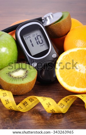 Glucose meter, medical stethoscope, fresh ripe fruits and tape measure, orange kiwi apple, concept of diabetes and healthy lifestyles - stock photo
