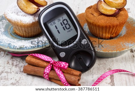 Glucose meter, muffins with plums powdered sugar and cinnamon on old rustic wooden background, diabetes and delicious dessert, result of measurement of sugar - stock photo