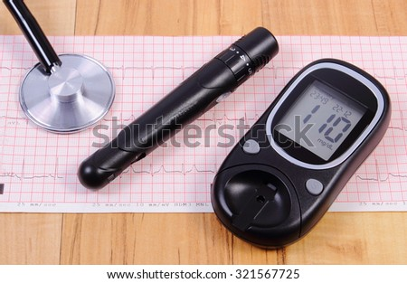 Glucose meter with lancet device and medical stethoscope lying on electrocardiogram graph, ecg heart rhythm, medicine and health care concept - stock photo