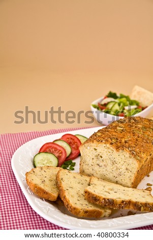 gluten free bread on plate surrounded by salad and vegetables - stock photo