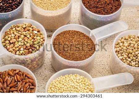 gluten free grains (quinoa, brown rice, kaniwa, amaranth, sorghum, millet, buckwheat, teff) - measuring scoops on a rustic barn wood - stock photo