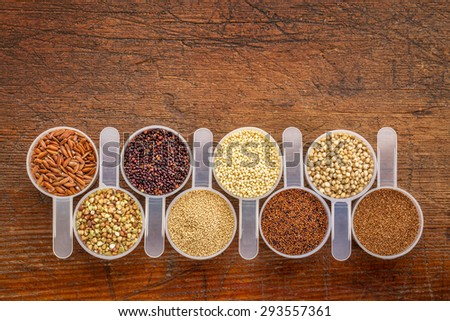 gluten free grains (quinoa, brown rice, kaniwa, amaranth, sorghum, millet, buckwheat, teff) - a row of measuring scoops on a rustic wood with a copy space