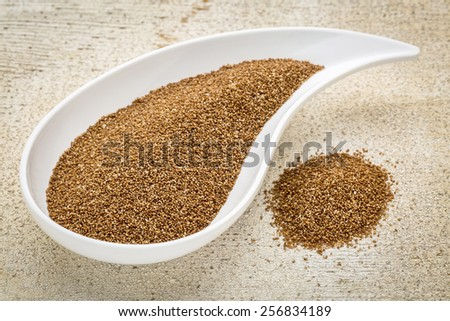 gluten free teff grain on a teardrop shaped bowl against white painted grunge wood - stock photo