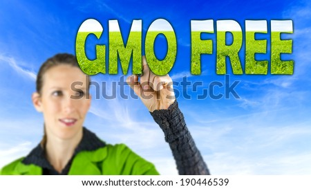 GMO Free conceptual image with a girl reaching up to touch text - GMO Free - in letters of green grass against a blue sky depicting cultivating healthy farm crops that are free of genetic modification - stock photo