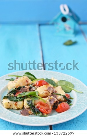 gnocci with spinach and cherry. - stock photo