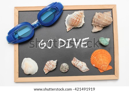 Go Dive text on chalk board with swimming goggle and shell - vacation and business concept - stock photo