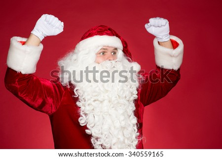 Go for it. Half length studio portrait of cheering Santa screaming from excitement with his hands raised up in the air - stock photo
