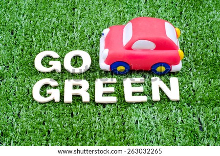 Go Green Concept with text and toy car on artificial grass - stock photo