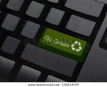 Go green key with wind turbine icon on laptop keyboard - stock photo