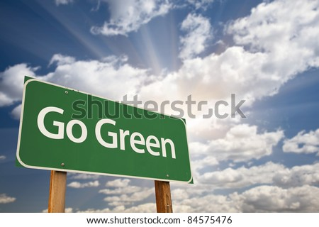 Go Green Road Sign Against Dramatic Clouds, Sky and Sun Rays. - stock photo