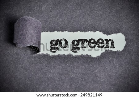 go green  word under torn black sugar paper  - stock photo